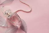 Женские духи в флаконе. Розовый фон.