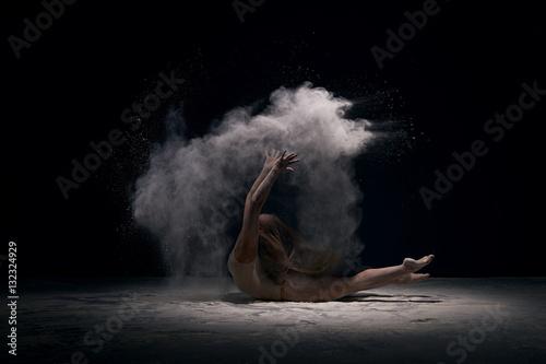 Tuinposter Gymnastiek Gymnast in ecru bodysuit in cloud of white dust