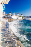 Splashing waves and famous Mykonos windmills in golden afternoon light, Mykonos island, Cyclades, Greece - 132330975
