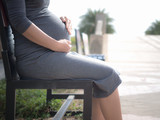 Pregnant woman sitting on a bench In the park. in the morning.
