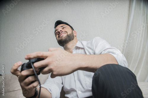 Poster young trendy male gamer playing with a joystick
