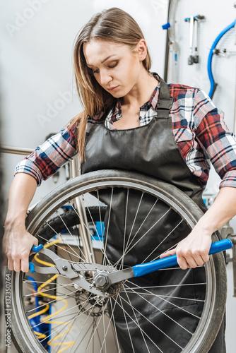 Deurstickers Fietsen Mindful craftswoman fixing the wheel in the workshop