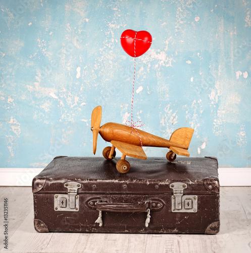Holzflugzeug mit Herz auf alten Koffer