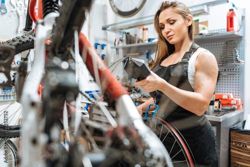 Deurstickers Attentive charming craftswoman weighting the wheel in the garage