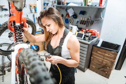 Deurstickers Cheerful female master repairing the mountain bicycle