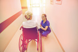 nurse with senior woman in wheelchair at hospital