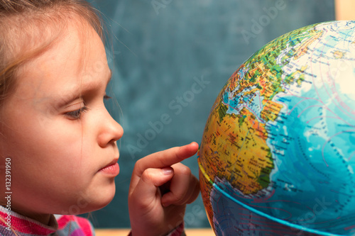 Plakat girl - a child of seven years on the geography lesson near  globe  the world aga