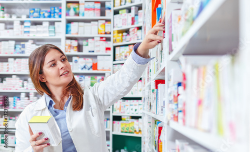 Staande foto Apotheek Photo of a professional pharmacist checking stock in an aisle of a local drugstore.