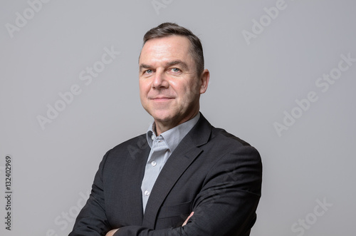 Confident middle age businessman over gray Poster