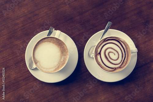 Poster Two cups of coffe on wooden table.