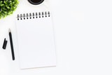 Blank notebook page is on top of white office desk table. Top view with copy space, flat lay.