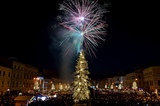 New Year`s Eve firework behind Christmas tree. Celebrating 2017 in Banska Bystrica, Slovakia. Multicolor explosion on dark sky. Foundation day of Slovak republic