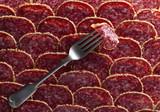 Old fork and salami sausage slices