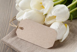 white tulips on wood table with paper tag for yout text