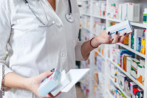 Papiers peints Pharmacie Woman pharmacist holding prescription checking medicine in pharmacy - drugstore.
