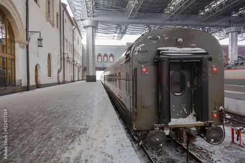 Poster Railway station with passenger train in the snow winter