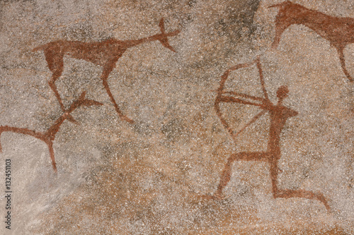 Drawing on a rock cave wall ocher paint, ancient prehistoric Neanderthal man. man surrounded by prehistoric animals, head of intelligence, radiance, lord
