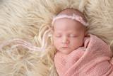 Новорожденная малышка в розовой обмотке и повязке с цветком спит на меховом пледе