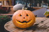 The smiling Halloween pumpkin is on a wooden surface