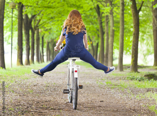 Poster Young woman riding a bike at the park with her legs in the air