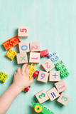 Child playing with wooden cubes with numbers and colorful toy bricks on a turquoise wooden background. Toddler learning numbers. Hand of a child taking toys. - 132521537