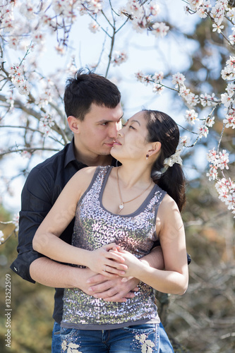 Poster Asian girl and european guy kissing among of blossoming almond b