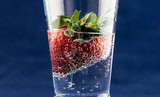 Strawberry in glass of carbonated gas soda water with bubbles