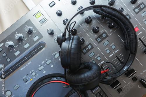 Poster DJ Mixer with headphones.