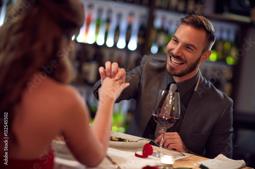 Poster Very happy man engaged girlfriend in restaurant