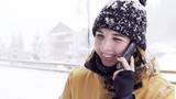 Closeup portrait of a girl talking on her phone and laughing outside. It is snowing.