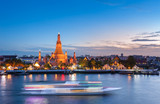 The boat was sailing in Chao Phraya River, background Wat Arun at sunset time ,Bangkok, Thailand. The Temple of Dawn
