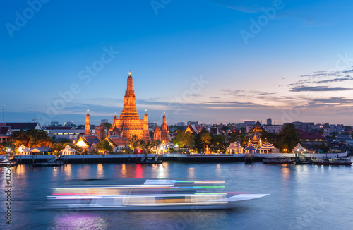 The boat was sailing in Chao Phraya River, background Wat Arun at sunset time ,Bangkok, Thailand Poster