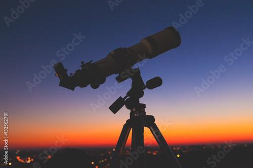Silhouette of a telescope with de-focused city lights. - 132562701
