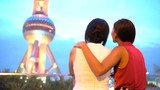 China Shanghai women taking selfie photo with smart phone by Oriental Pearl Tower at night. Happy young Chinese mom and daugther smiling and laughing having fun on travel at famous tourist attraction.