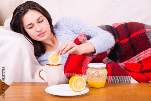 Poster sick girl under a blanket treated tea with lemon