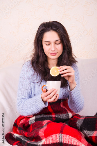 Poster sick girl sits under a blanket and treated tea with lemon