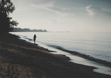Silhouette of woman walking on the beach background with vintage filter