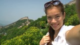 Selfie video. Girl tourist at Great Wall of China at famous Badaling during travel holidays at Chinese tourist destination.