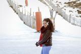 Vacaciones en la nieve. Mujer joven a los pies de la pista de esquí