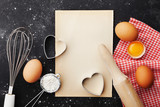 Baking background with flour, rolling pin, eggs, paper sheet and heart shape on kitchen black table top view for Valentines day cooking. Flat lay style.