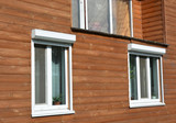 Windows with rolling shutter protection on the wooden house facade exterior - 132599160