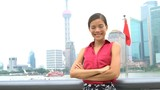 Business woman portrait in Shanghai, China showing Pudong financial district and Chinese flag in background. Proud happy smiling young successful corporate executive or professional businesswoman.