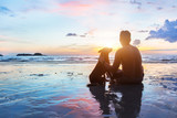 friendship concept, man and dog sitting together on the beach at sunset - 132617391