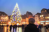 people in christmas market, woman looking at the decorated illuminated tree, festive new year lights in Strasbourg, France, Europe - 132620762