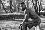 Muscular Shirtless Hunky Black Man Outdoor in City Park. Showing Healthy Muscle Body While Looking at Camera