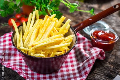 Poster Homemade french fries on wooden  background