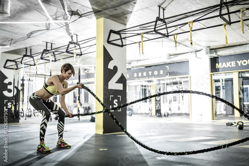 Póster Girl does exercise with fitness rope in gym