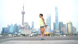 Runner stretching thighs after workout in Shanghai, China on famous boardwalk with skyline. Urban city lifestyle. Active Asian woman training outside on the Bund doing leg exercises muscle stretches.