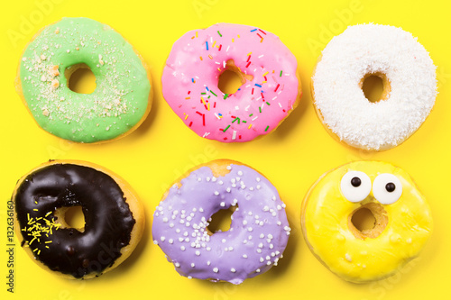 Pink round donut and few other on yellow background. Flat lay, top view.
