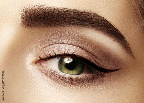 Perfect shape of eyebrows, brown eyeshadows and long eyelashes. Closeup macro shot of fashion smoky eyes visage